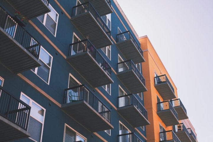 Blå og oransje husfasader med vinduer og balkonger