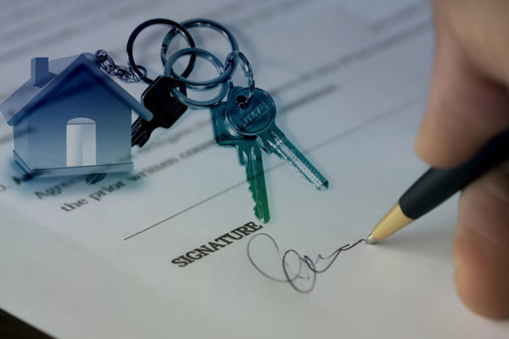 Person signerer kjøpsdokumenter for bolig.