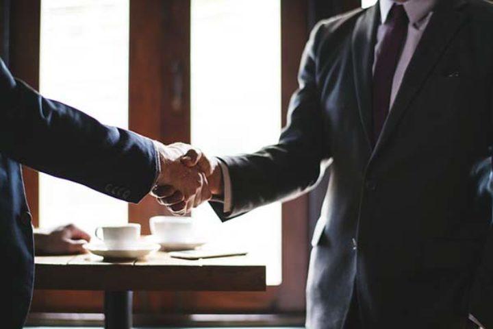 Fotografi av to menn i dress som tar hverandre i hendene