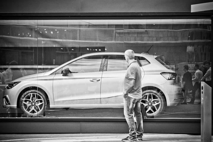 Sort/hvitt bilde av mann som ser på bil i utstillingsvindu