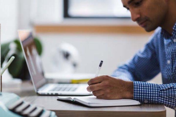 Mann skriver i notatbok på skrivebord med pc
