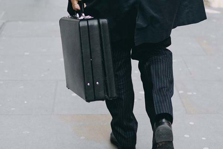Mann i dress med koffert