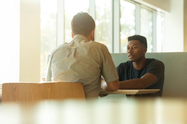 To menn som sitter overfor hverandre ved et bord og snakker sammen.
