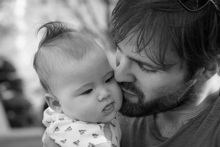 Pappa kysser babyen sin på kinnet