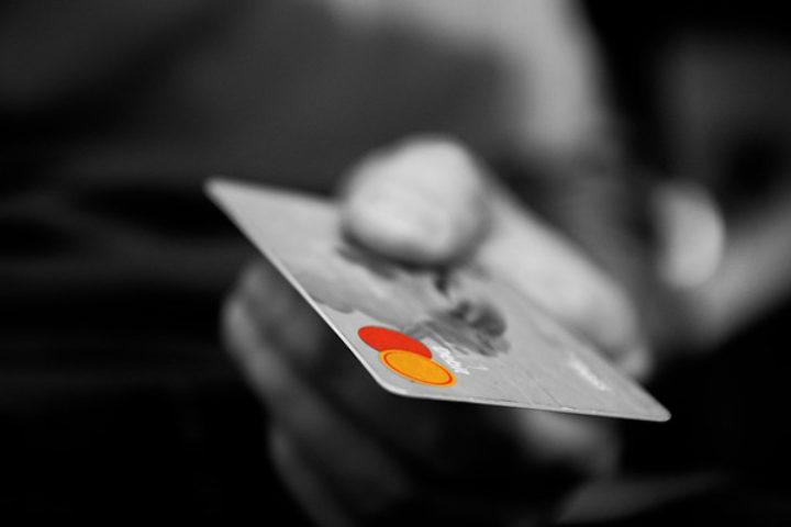 Sorthvitt bilde med Mastercard i forgrunnen, logo i farger. Vi hjelper deg ved pengekrav.