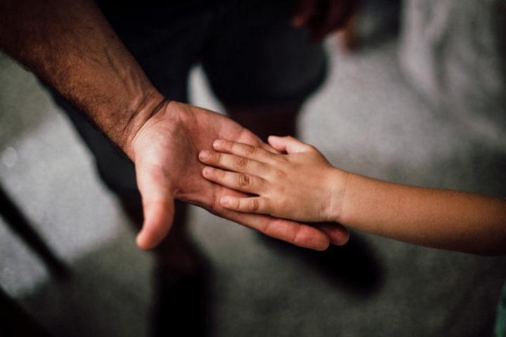 Barnehånd oppå voksen manns hånd