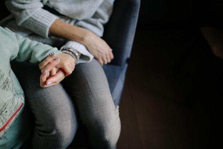 Barn og voksen holder hender