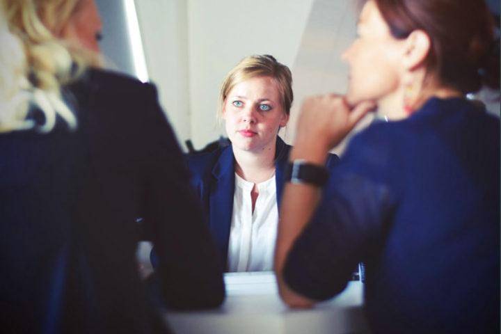 Fotografi av tre kvinner som snakker sammen